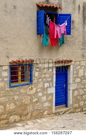 Laundry Driying In Sun, Blue Windows And Blinds