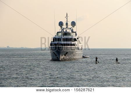 a luxury white cruise yacht in Maldives ocean and serfing board with serfer on it