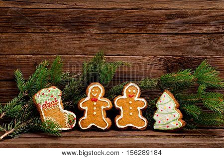 Gingerbread: sock Christmas tree gingerbread men. Fur-tree branch against the background of a wooden wall with space for text