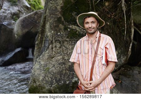 Outdoor Shot Of Bearded Caucasian Ecologist Or Botanist In Panama And With Briefcase Holding Manual