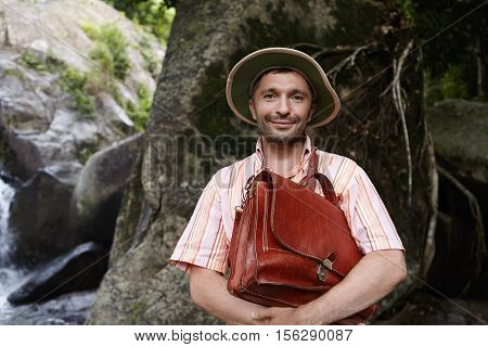 Middle Aged Bearded Caucasian Botanist Or Biologist Wearing Panama Hat, Holding Briefcase With Both