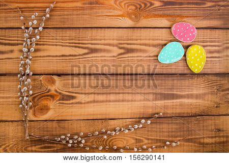 Bright Spring.Happy easter. Easter background. Easter cookies. Gingerbread in the form of crimson turquoise and yellow Easter eggs on a background of brown wooden desk and willow branches. Free space