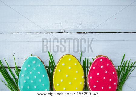 Bright Spring. Happy easter. Easter background. Easter cookies. Gingerbread in the form of crimson turquoise and yellow Easter eggs on green grass on a background of white wooden desk. Free space