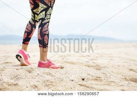 Sports And Healthy Lifestyle Concept. Cropped Shot Of Legs Of Girl Athlete Against Ocean Beach. Fema
