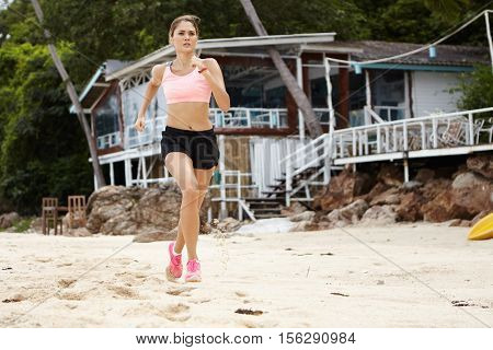 Full Length Portrait Of Blonde Female Runner In Sportswear And Pink Sneakers Jogging On Beautiful Sa