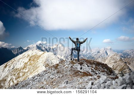 happy mountain hiker is standing on a top of a mountain