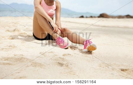 Young Woman Jogger With Beautiful Fit Legs Sitting On Sandy Beach And Relaxing During Break After Ha