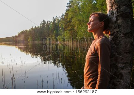 a young woman standing on a tree enjoying peaceful moment of sunset. In the reflection of the lake water sees clouds and sun.