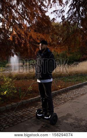 Young man riding electrical scooter - hoverboard in the city park