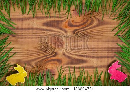 Happy easter. Easter background. Summer. Easter cookies. Gingerbread in the form of crimson and yellow Easter rabbits on green grass on a background of brown wooden desk. Free space