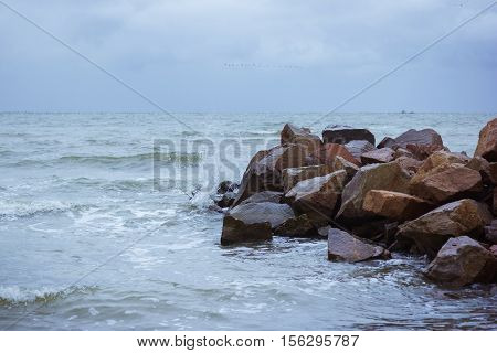 Windy and cold weather at sea. Sea waves on the rocks. Sea spray and foam. Large wet stones
