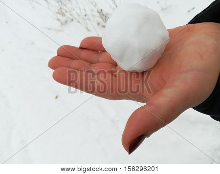 Snowball on a beautiful female hand on white background