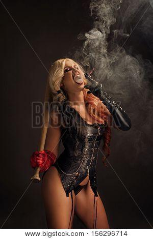 Sexy harlequin woman with bat on dark background