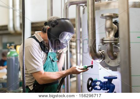 Industrial worker with protective mask welding inox elements in steel structures manufacture workshop or metal factory.