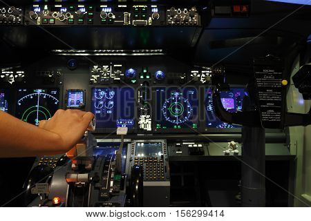 Hand on controller in pilot room of flight simulator