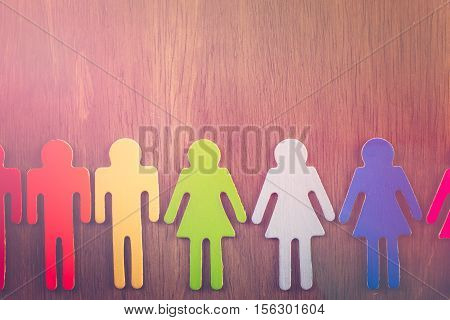 Rainbow Gay Pride male and female figures on wood background.