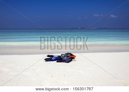 Snorkeling equipment lying on a white sand beach near the turquoise water, a heavenly scene taken on the amazing island Meedhuparu, Raa Atol, Maldives, November 2016.