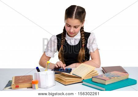 young cute schoolgirl in unform doing homework isolated on white background poster