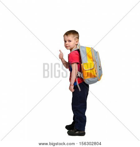 full length of young schoolboy with schoolbag looking at the camera and showing thumbs up isolated on white background