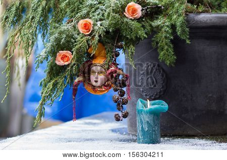 Closeup Christmas-tree branch with decoration Venetian Harlequin and tender roses in the snow on thr blue background