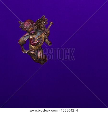Christmas concept. Bronze decorative statue of a flying angel with lute on purple background.