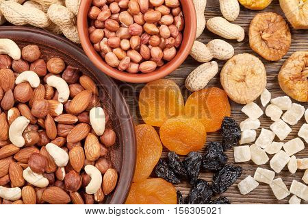 Different nuts and dried fruits on a wooden table. Almond hazelnut peanuts and cashew. Background with nuts and fruits.