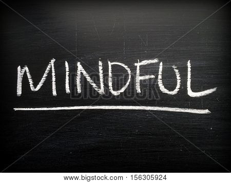 The word Mindful written by hand in white chalk on a blackboard as a reminder to be aware of your thoughts and sensations
