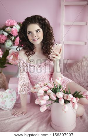 Beautiful Young Teen Girl Portrait With Curly Hair Use Mobile Phone. Brunette In Pink Dress Over Bou
