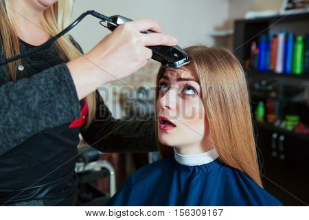 Young female afraid  the machine for hair.