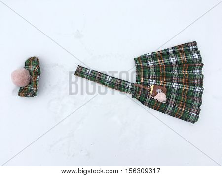 costume in Scottish style, green, brown plaid, the costume consists of skirt with pleats and hanging on belt bag with tassel, beret with pompom pale pink, in the snow painted the silhouette of a man, face, body, hands