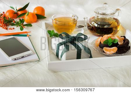 Green mint tea, mandarin slices, chocolate and gift box on tray, near notebook, pens, mobile, mandarins, mountain ash sprig on white artificial fur background. Happy time break and gift. Close.