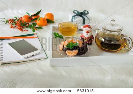 Green mint tea, chocolate, mandarin slices and Santa Claus on tray near mobile, notebook, pencil, mandarins, mountain ash on white artificial fur background. Time break Christmas surprise preparation.