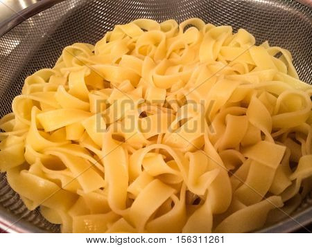 Italian pasta boiled in pan on stove image for food blog cook book restaurant business concept