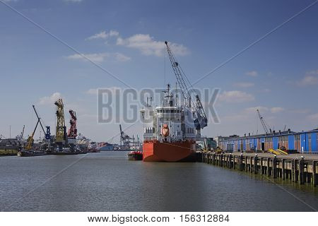 industrial ship with a life boat at a sunny day get unloaded in the port of rotterdam