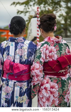 KYOTO, JAPAN - OCTOBER 8, 2016: Unidentified women in traditional clothes in Fushimi Inari shrine in Kyoto Japan. This popular shrine have 32000 sub-shrines throughout Japan