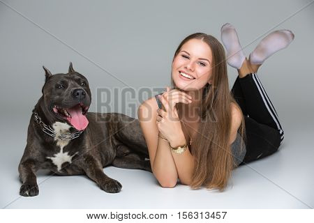 Beautiful sporty young woman lying on floor with adult grey amstafford terrier dog. Studio shot over gray background. Copy space.