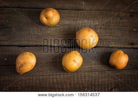 Fresh potato tubers on the old wooden table. Top view.