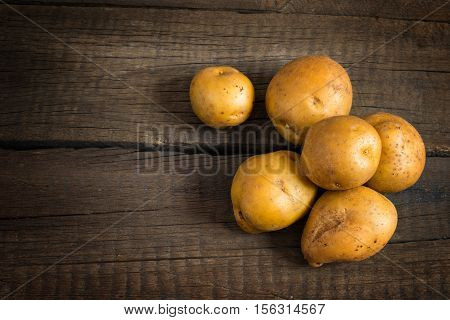 Fresh potato tubers on the old wooden table. Top view with copy space