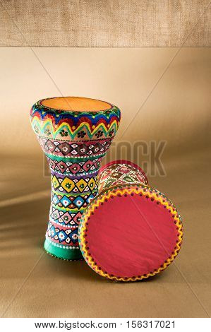 Two decorated colorful pottery goblet drums (chalice drum tarabuka darbuka) on background of wooden table with vanishing shadow lines and sackcloth wall. Low light studio shot