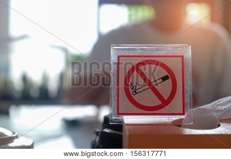 No smoking sign with man blurred background.