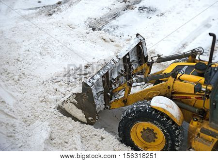 Yellow tractor shoveling snow on the street.