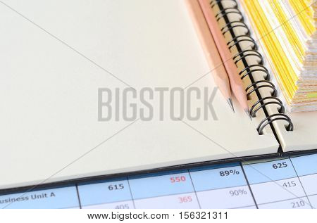 Wooden pencils and financial statements on blank note book with copy space for writing your idea.