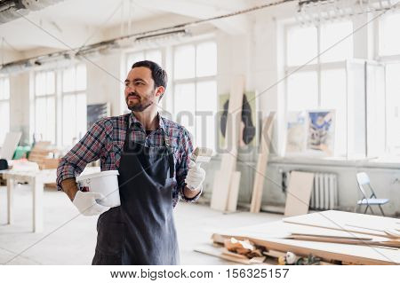 Painter with a can and brush at his work room.