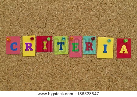 Criteria word written on colorful sticky notes pinned on cork board.