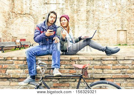 Teenage couple using phone and notebook outdoor at winter time - Best friends looking internet content sitting on old urban wall - Concept of young people lifestyle with modern technologies and trend