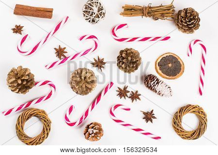 Christmas sweet candy canes and fir cones on white background wallpaper