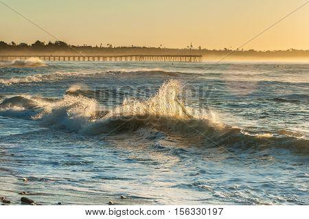 Back lit shore break waves with Ventura Pier in glowing background.