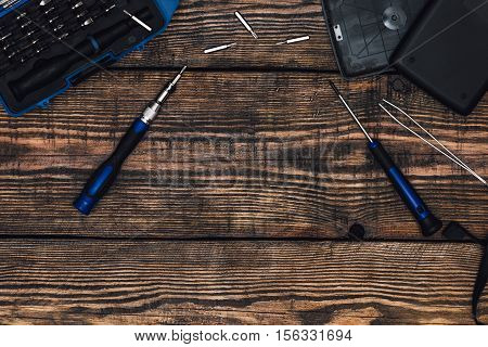Precision Screwdriver and Some Tools on Wooden Table with Place for Text