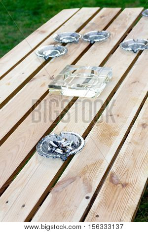 Glass ashtray on a wooden table. Ashtray with cigarette butts.
