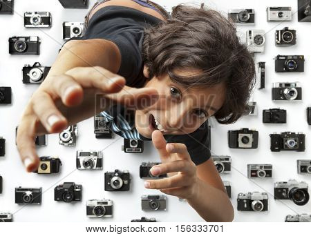 Leiden, Netherlands, 10-19-2016, Greedy boy reaching for another camera among a collection of old analog different camera's